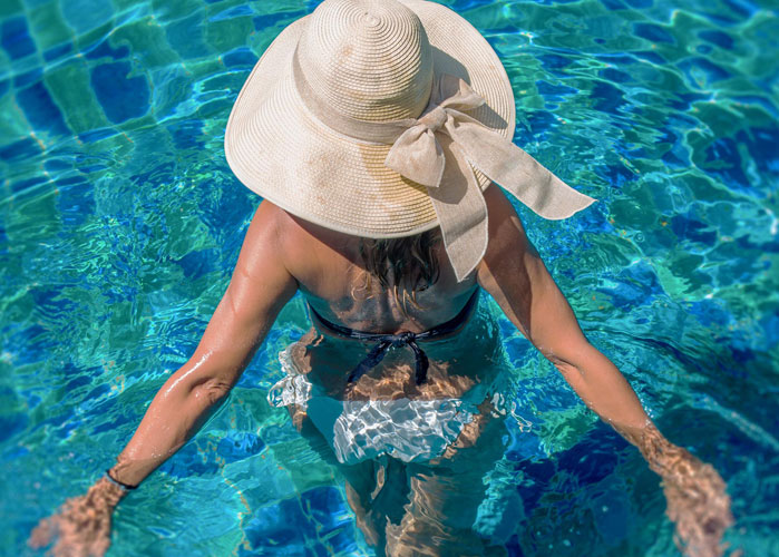 woman standing in swimming pool with large hat - newark de apartments