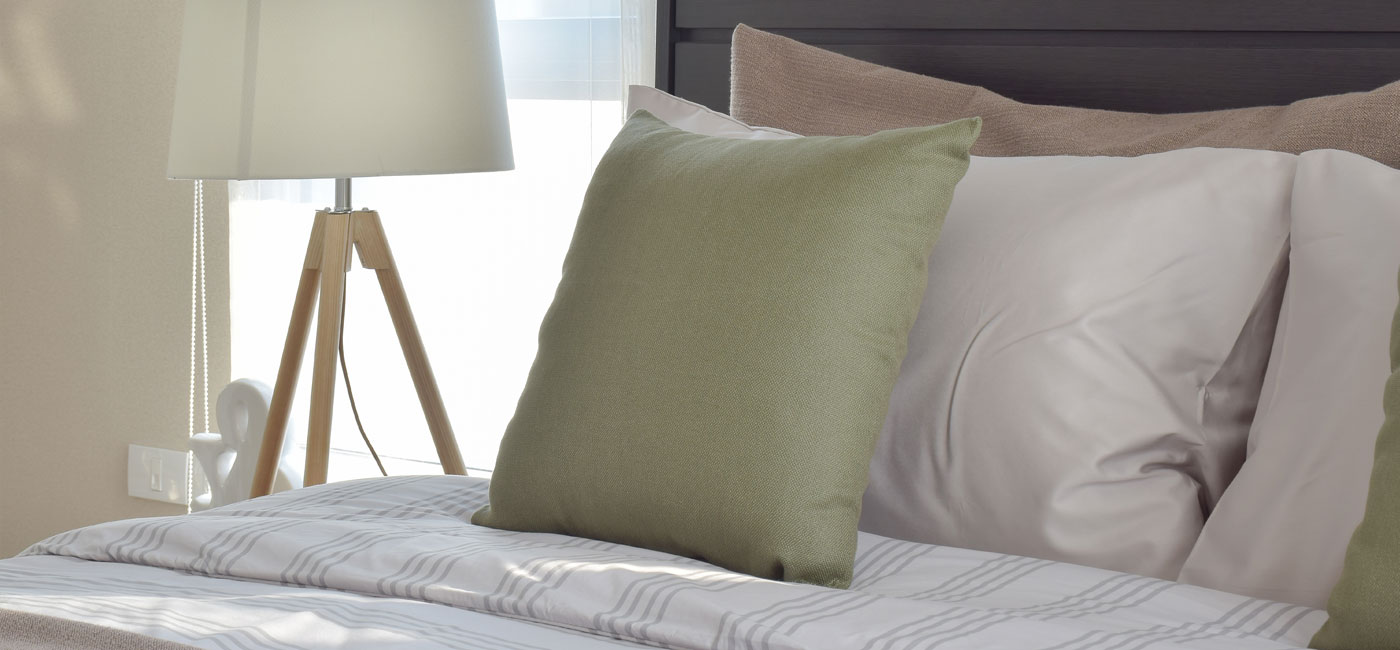 bed with fluffy pillows, night stand, modern lamp and window - newark de apartments