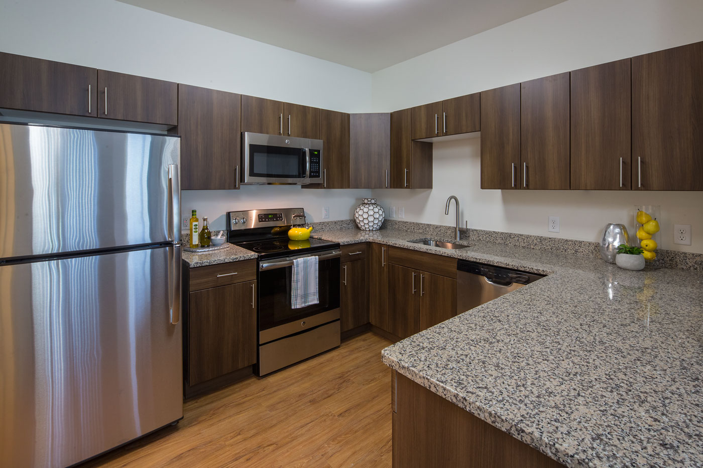 large kitchen with contemporary cabinetry, granite countertops, stainless steel appliances and plank flooring - newark de luxury apartmentsok a gourmet meal in the modern kitchens of our Christiana DE apartments