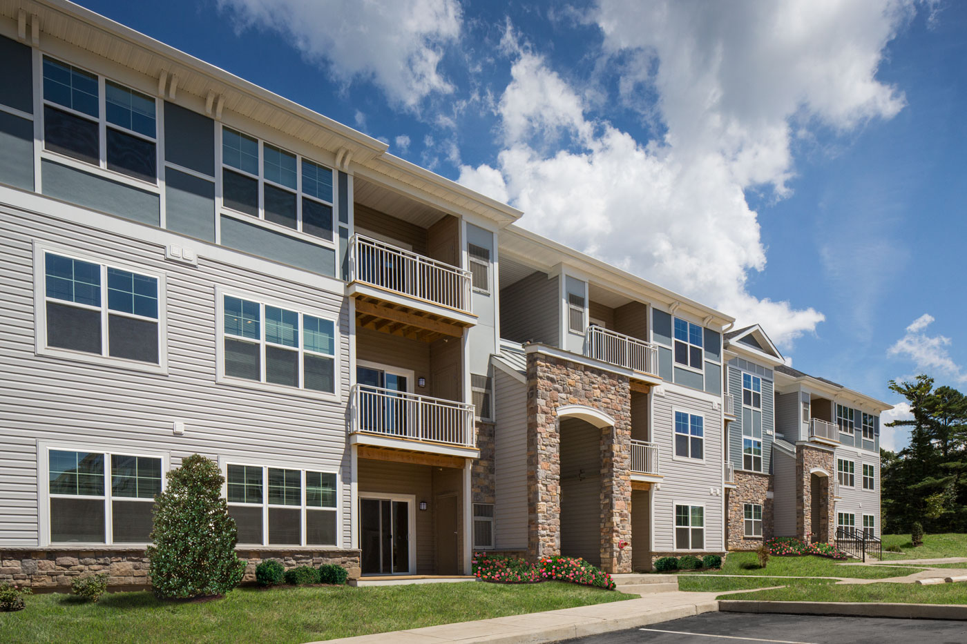 exterior of apartment building with green lawn, bushes and flowers - apartments near christiana mall