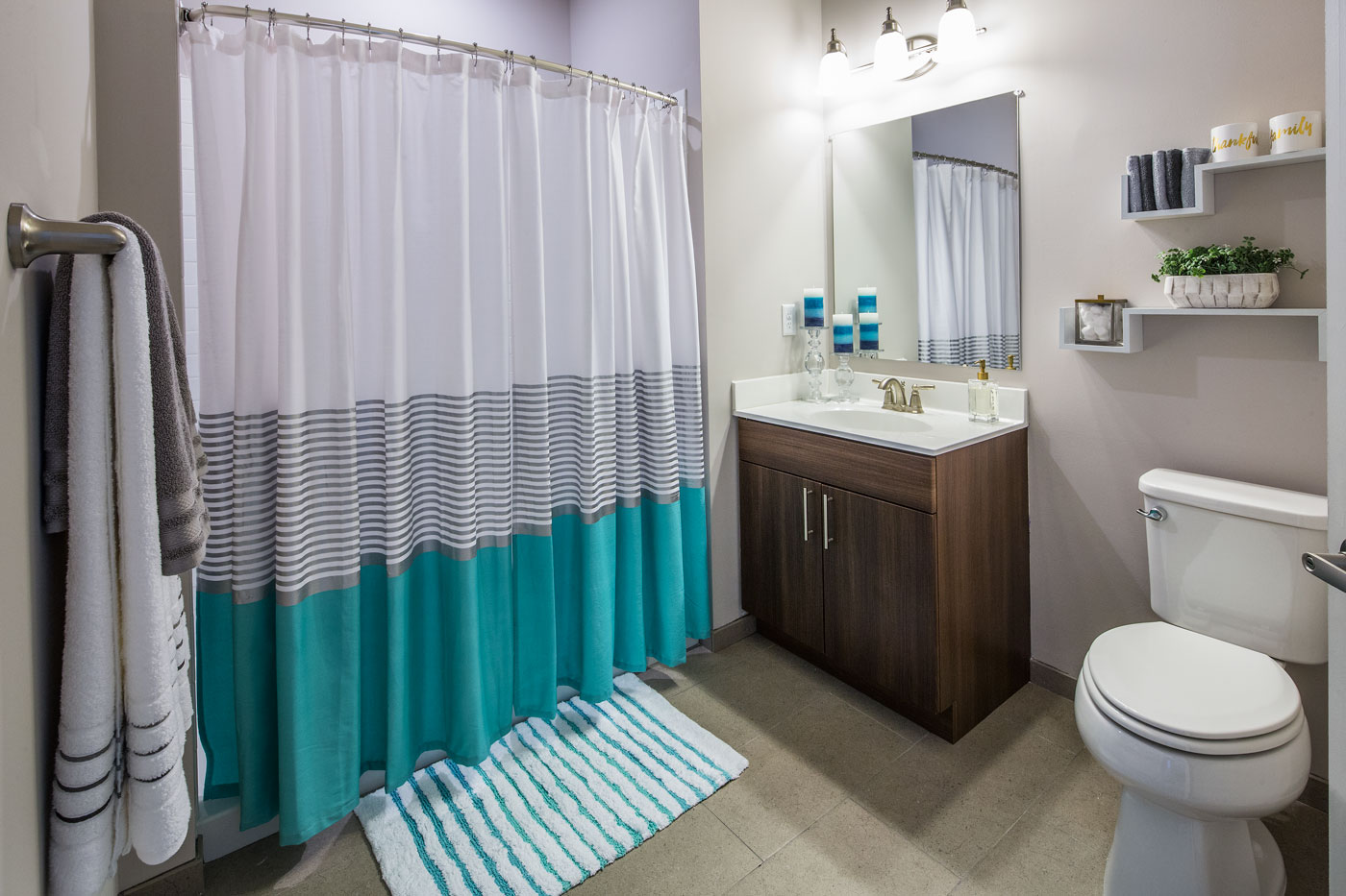 bathroom with vanity, walk in shower, large mirror, shelving, and toilet - apartments near christiana mall