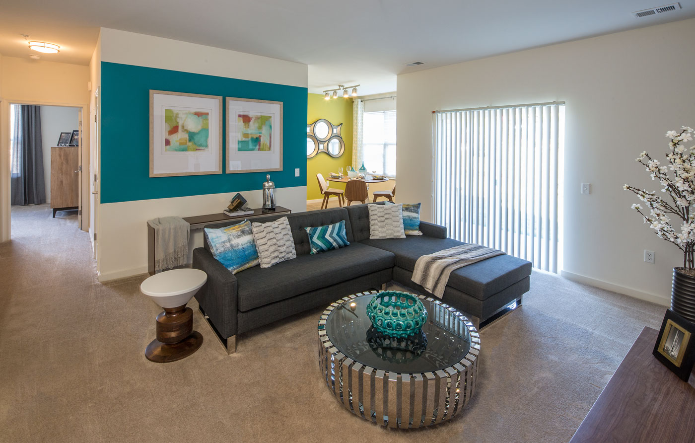living area with sectional sofa, coffee table, end tables, modern artwork and view of dining area - christiana mall luxury apartments