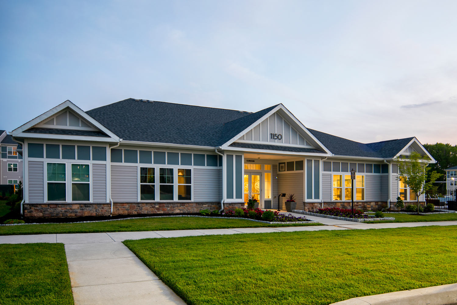 exterior of clubhouse with meticulously manicured lawn - newark de apartments