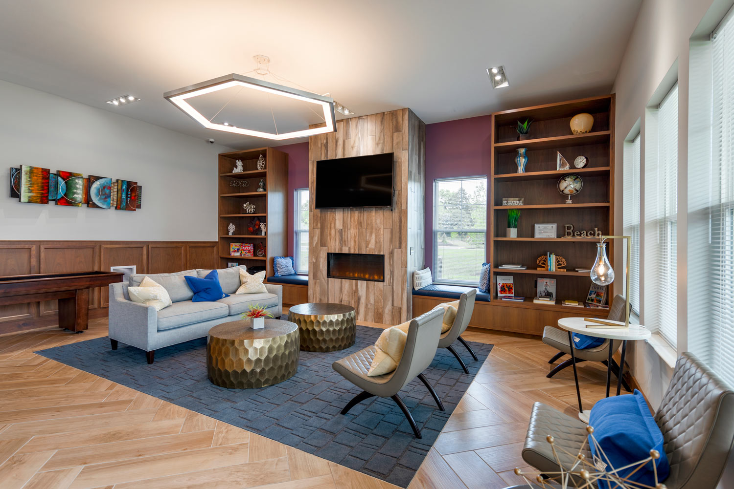 clubhouse lounge with sofa, chairs, bookshelves, fireplace and tv - luxury Christiana DE apartments