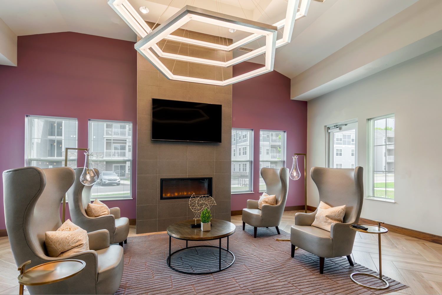 clubhouse with seating area, tables, chairs, modern lighting, flat screen television, and fireplace - luxury apartments near christiana mall