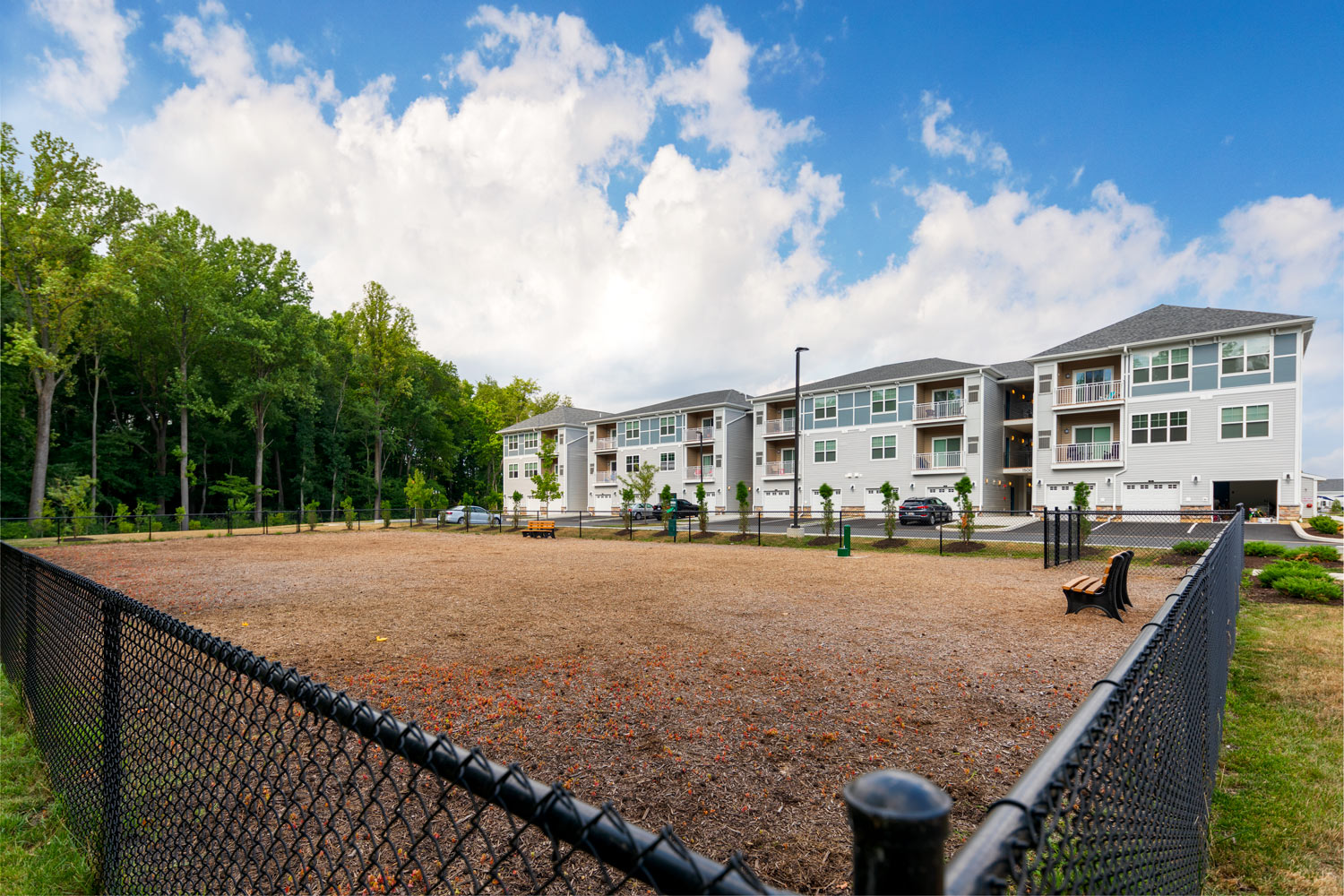 fenced in dog park with apartment buildings in the background - christiana mall apartments