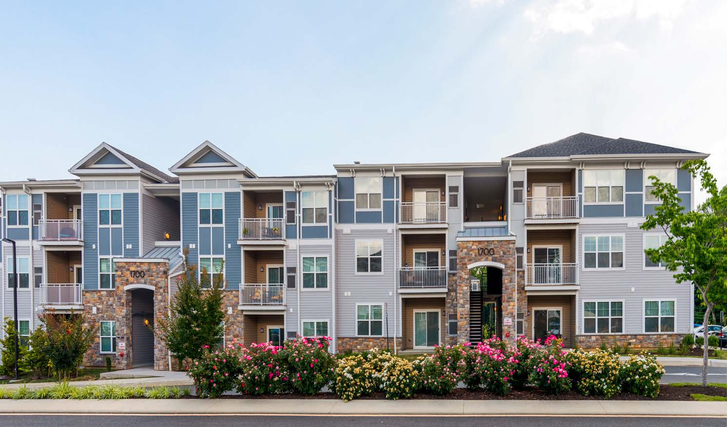 emblem exterior with trees and flowers - luxury apartments in newark de