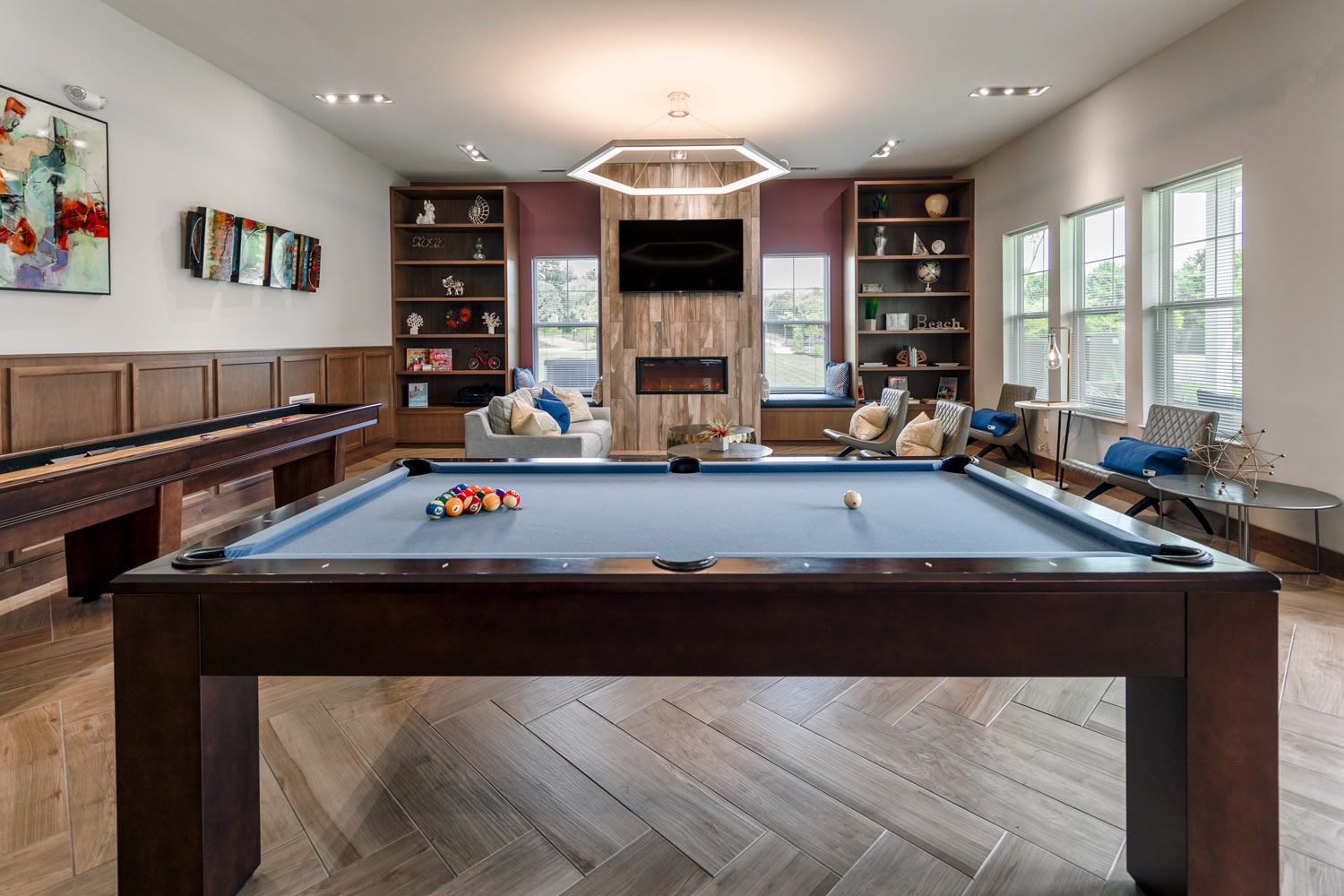 clubhouse with seating area, billiards, shuffleboard, fireplace, flat screen tv and large bookshelves - newark de luxury apartments