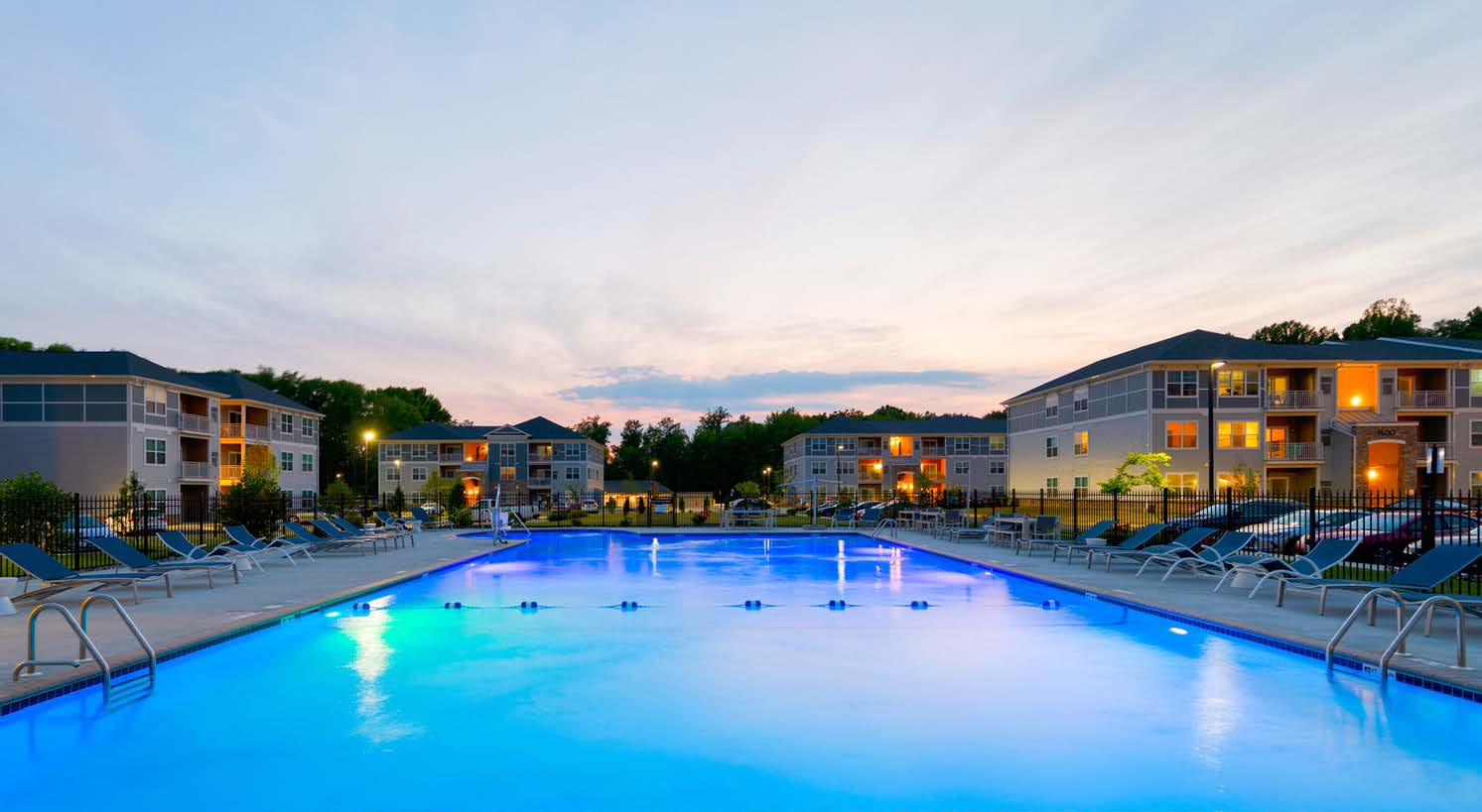 resort style pool, chaise lounge chairs at dusk with apartment building in the background - newark de luxury apartments