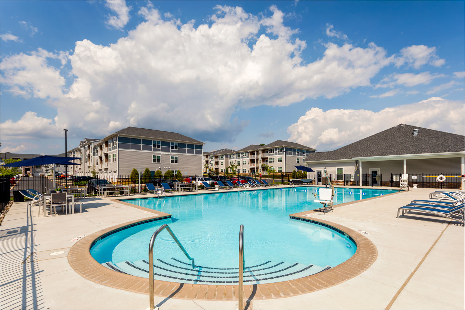 resort style pool, chaise lounge chairs, with apartment building in the background - newark de luxury apartments