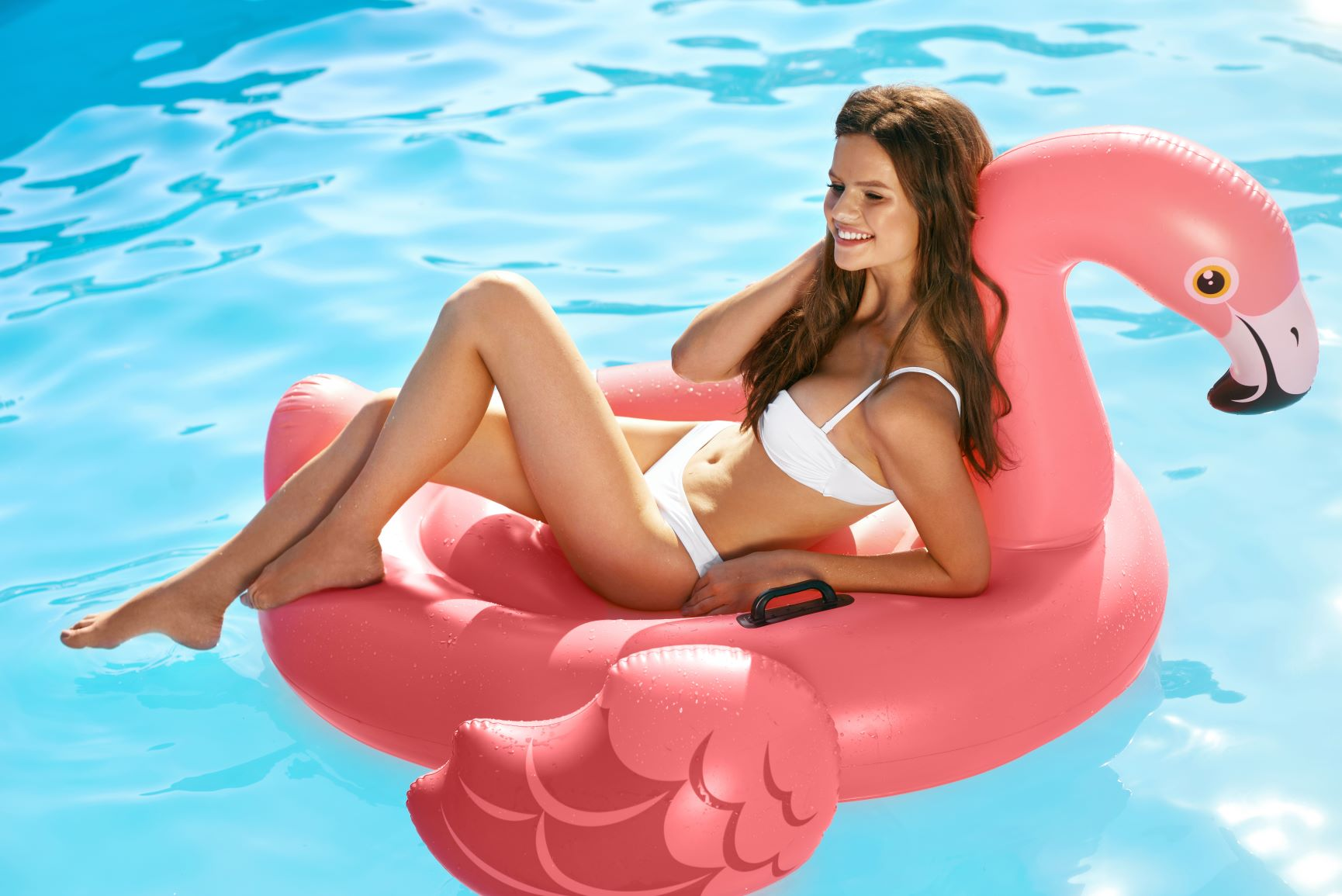 woman on flamingo shaped float in swimming pool - christiana de apartments