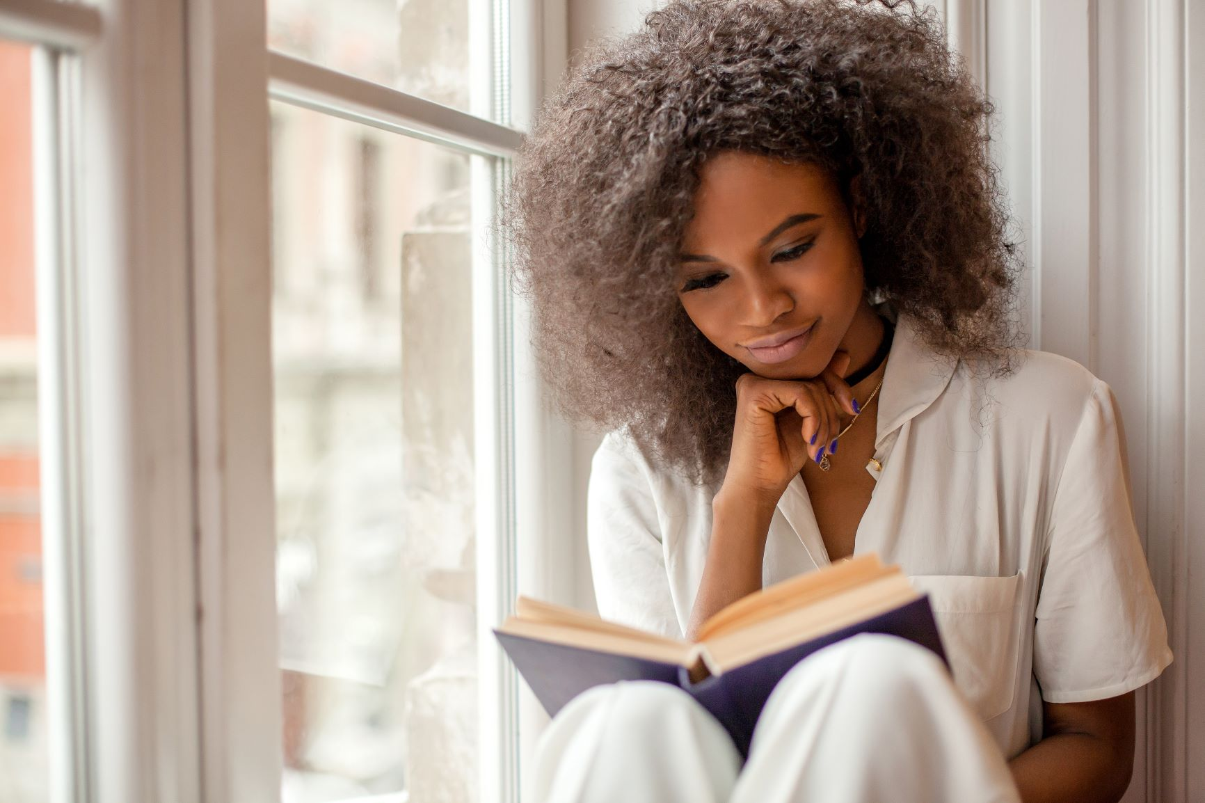 won sitting by window reading a book - christiana de apartments